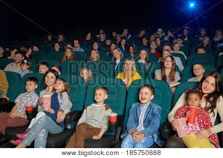 Cute little kids smiling and laughing while watching a cartoon at the local movie theatre people entertaining excitement expressive funny laughter enjoyment elementary lifestyle leisure concept.
