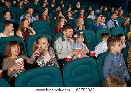 Cinema auditorium full of kids and their parents enjoying premiere of a comedy movie on a weekend happiness positivity leisure emotions excitement amazement entertaining concept.