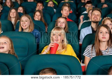 Beautiful young girl smiling drinking coke at the movie theatre enjoying watching film with her friends and classmates children people entertainment comfort weekend holidays concept.