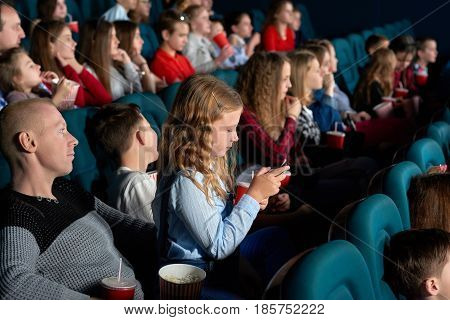 Little girl typing on a mobile phone while sitting at the cinema watching a movie technology mobility connectivity connection entertainment boredom distracting distraction gadget smart phone concept.