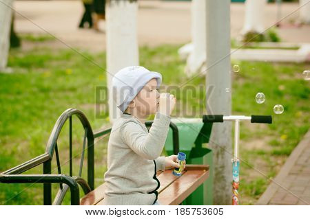 fashionable boy blowing bubbles in a city park
