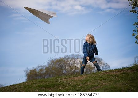 Cute kid boy launching paper airplane in the park. Small child having fun and playing with big handmade plane. Activities with children outdoors. Lifestyle