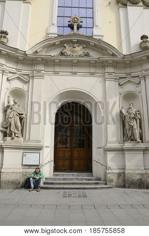 GRAZ, AUSTRIA - MARCH 19, 2017: Beggar at the entrance of Parish Church in Herrengasse street in Graz Austria