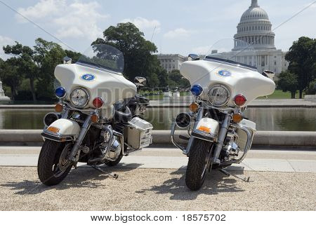 Two Secret Service motorcycles parked in front of The Capitol in Washington, DC.