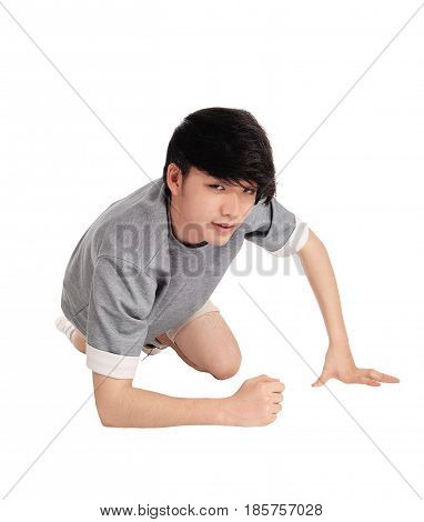 A good looking Asian teenager in a gray t-shirt kneeling on the floor in the studio in shorts isolated for white background.