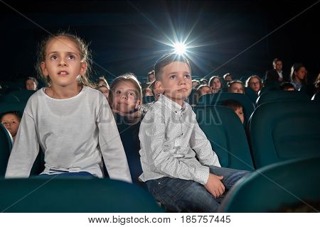 Low angle shot of little kids watching movie at the cinema looking amused and interested copyspace lens flare light childhood leisure activity people holidays carefree fascination concept.
