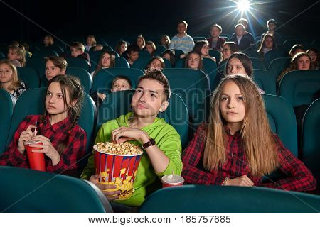 Two girls and one boy enjoying a movie together at the cinema eating popcorn from a bucket friends friendship togetherness classmates teens leisure entertainment holidays activity concept.