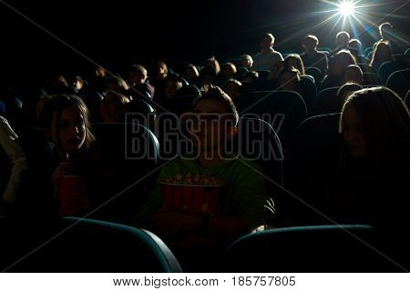 Shot of a dark cinema auditorium full of people watching a movie film projector light beam copyspace background lifestyle entertainment activity hobby leisure concept.
