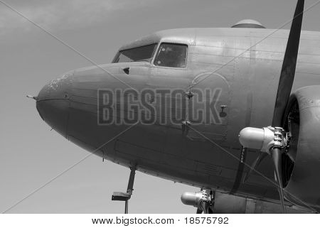 A Dakota (Douglas C-47) transport plane stands idle in the sunshine.