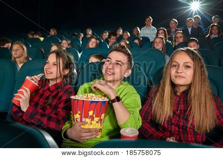 Beautiful young girls smiling to the camera while watching a movie at the cinema with her friends people children friendship togetherness weekend positivity living lifestyle classmates concept.