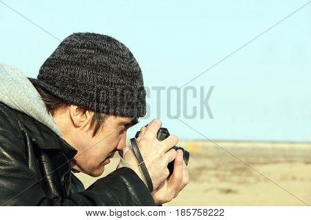 Photographer with retro photo camera taken closeup.