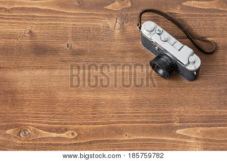 Camera on wooden background on one side