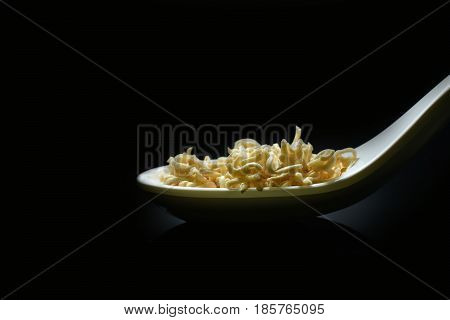 Instant noodles close-up on a spoon and dark background. (Instant noodles Raw)