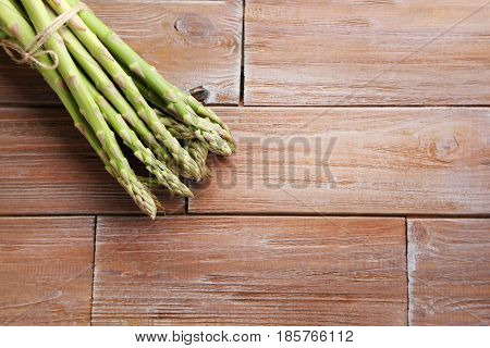 Heap Of Green Asparagus On Brown Wooden Table