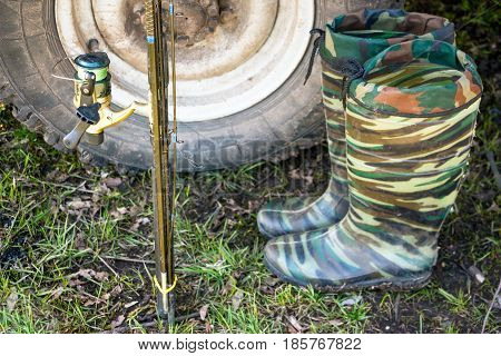 Fishing trip. Fishing accessories - fishing pole and boots