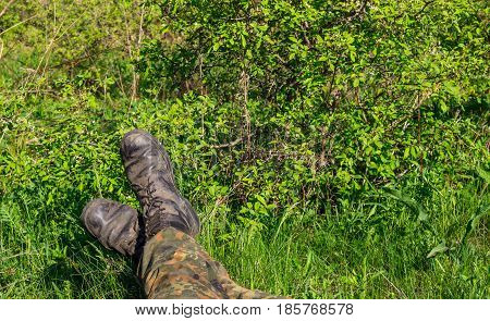 The tourist is sitting on the green grass stretching his legs you can see only the legs in soldiers' boots