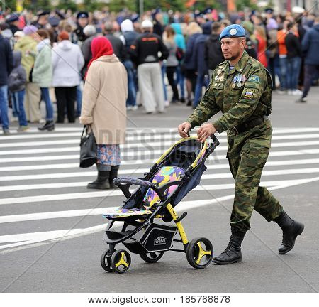 Orel Russia - May 9 2017: Celebration of 72th anniversary of the Victory Day (WWII). Man in paratrooper uniform with baby stroller square