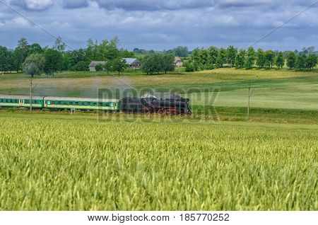 STEAM LOCOMOTIVE - Old train on a railway track among green fields
