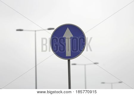 One way highway sign. Blue metal sign in front of highway lights on a daylight.