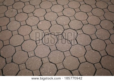 Vintage red stone street pavement in city walking zone. Hexagon texture.