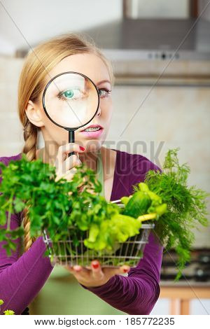 Buying healthy dieting food concept. Woman in kitchen having many green vegetables looking through magnifier at shopping basket trolley.