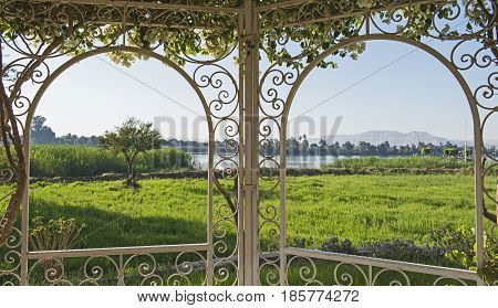 Rural Countryside View Of A River In Summer Through Trellis