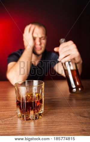 Drunk / Sad Man with Bottle and Glass of Liquor At Bar Counter