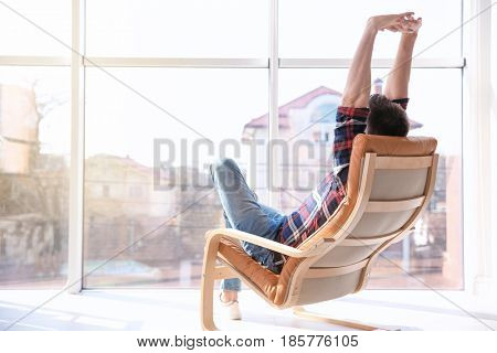 Happy young man sitting in armchair and stretching himself