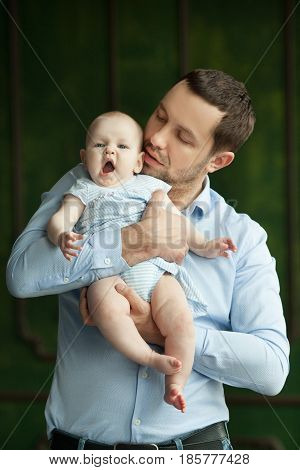 Happy dad of European appearance playing with little daughter