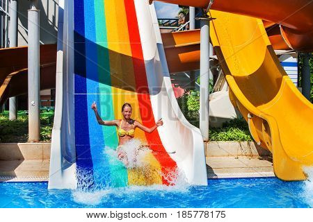 Swimming pool slides for children on blue water slide at aquapark . Summer kid ride holiday outdoor. Girl in two-piece swimsuit with hands up in aqua park. . Opening of new water park.