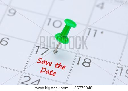 Save the Date written on a calendar with a green push pin to remind you and important appointment.