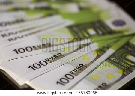 Paper money banknote bill of 100 euros on a black background