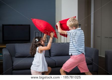 Siblings having pillow fight in living room at home