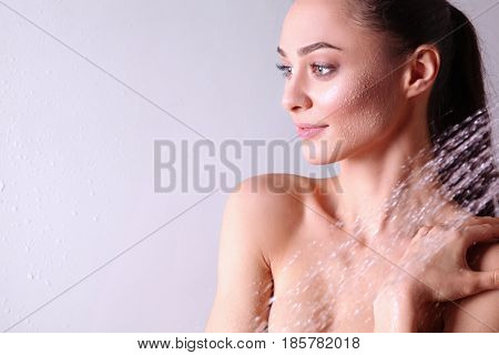 Young beautyful woman under shower in bathroom