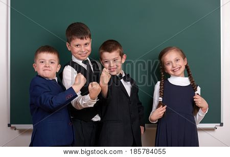group pupil as a gang, posing near blank chalkboard background, grimacing and emotions, dressed in classic black suit