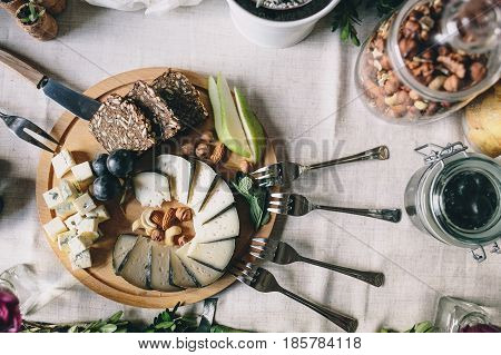 Sliced goat cheese with Dorblu with slices of bread, pears, grapes on a wooden plate. Nearby lie the fork, butter knife, a glass jar with hazelnuts. Top view