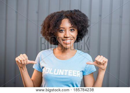 Portrait of a happy african ethnicity volunteer in blue t-shirt indoors