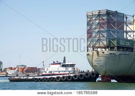 Oakland CA - May 09 2017: A tugboat maneuvers vessels by pushing or towing them. Tugboat PATRIOT pushing cargo ship KAUAI 180 degrees prior to docking at the Port of Oakland.