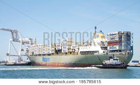 Oakland CA - May 09 2017: Cargo Ships are unable to maneuver sideways. Tugboats LIBERTY and PATRIOT push and pull to turn cargo ship KAUAI 180 degrees prior to docking at the Port of Oakland.