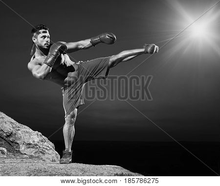 Black and white full length shot of a shirtless muscular man doing kickboxing training outdoors copyspace athletics physique fitness fit toned abs muscles strong powerful confident martial sportsman.