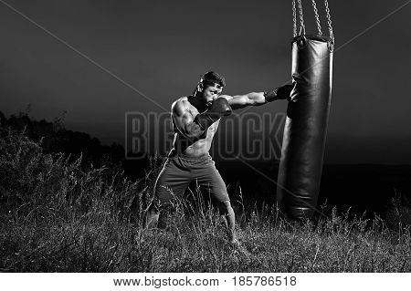 Monochrome shot of an aggressive young boxer hitting punching bag training outdoors copyspace masculinity nature fitness sports athlete athletics activity lifestyle body muscular toughness combat