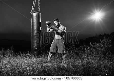 Monochrome portrait of a handsome young muscular male boxer training outdoors at night practicing on a punching bag copyspace nature alone sportsman competitive ambitious strong confident.