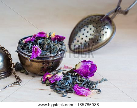 Tea strainer closeup tea leaves and rose buds selective focus
