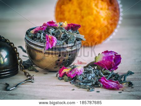 Close-up of tea strainer tea leaves and pink buds on a background of baked biscuit selective focus retro style