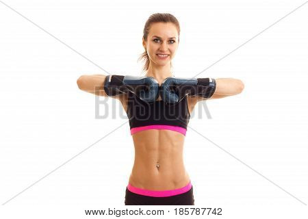 smiling young cute girl looks into the camera and holds hands in boxing gloves is isolated on a white background