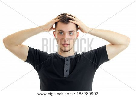 young serious guy kept his hands behind his head and looks directly isolated on a white background close-up