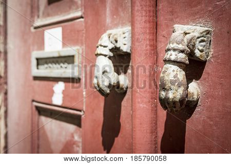 ancient rusty door knockers and a mailbox on an ancient red wooden door