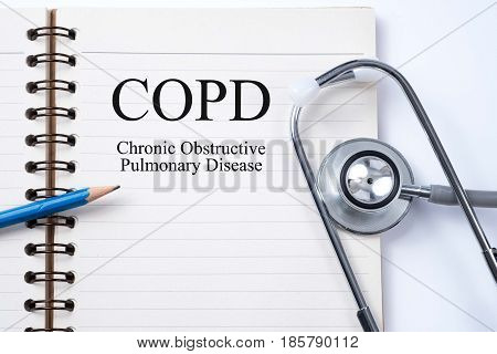 Stethoscope on notebook and pencil with COPD (Chronic obstructive pulmonary disease) words as medical concept.