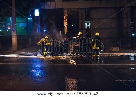 Firemen extinguishing a car fire on the street