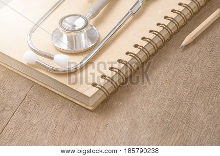 Medical concept : stethoscope on note book with sunlight on wood background